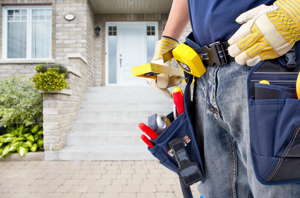 Picture of tools on a handyman's belt in front of a home